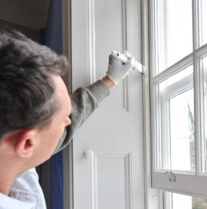 Man painting sash window frame