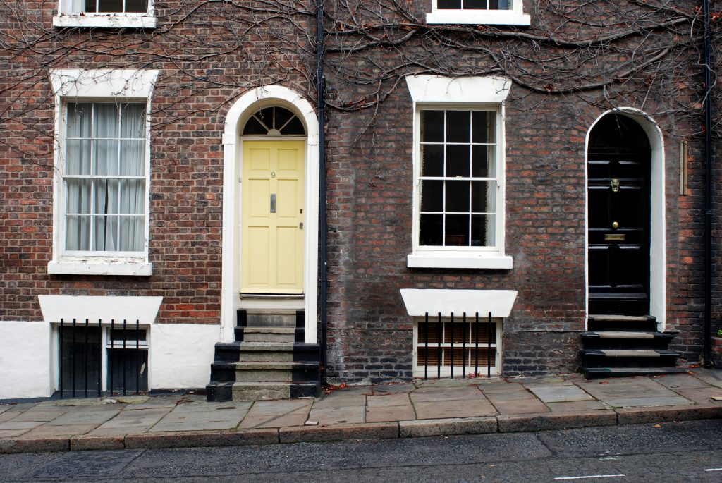 two houses with steps that have sash windows